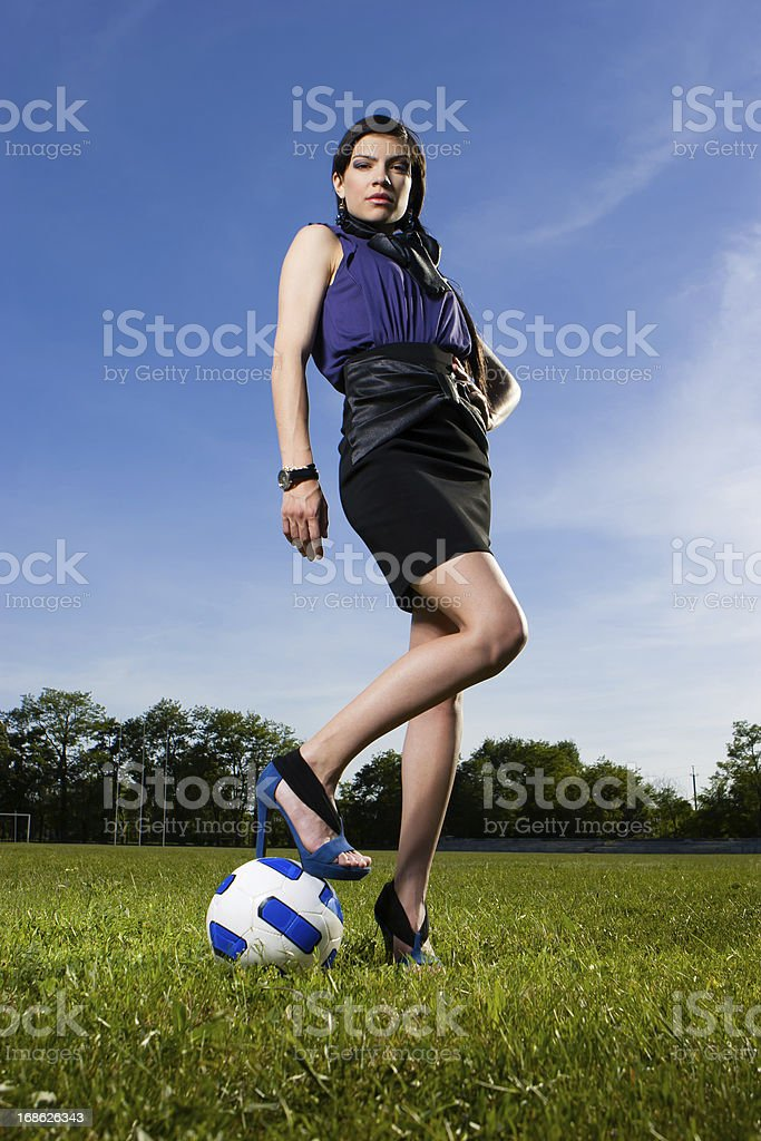 Beautiful young fashion girl on the soccer field stock photo