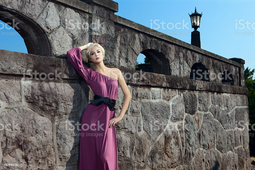 Beautiful Young Fashion Model in Purple Gown at Rock Wall stock photo