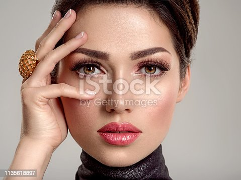 Beautiful young fashion woman with living coral lipstick. Attractive white girl wears luxury jewelry.  Glamour fashion model with bright gloss make-up posing at studio. Stylish fashionable concept.
