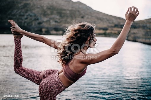 istock Beautiful young female adult doing yoga pose at lake 639333696