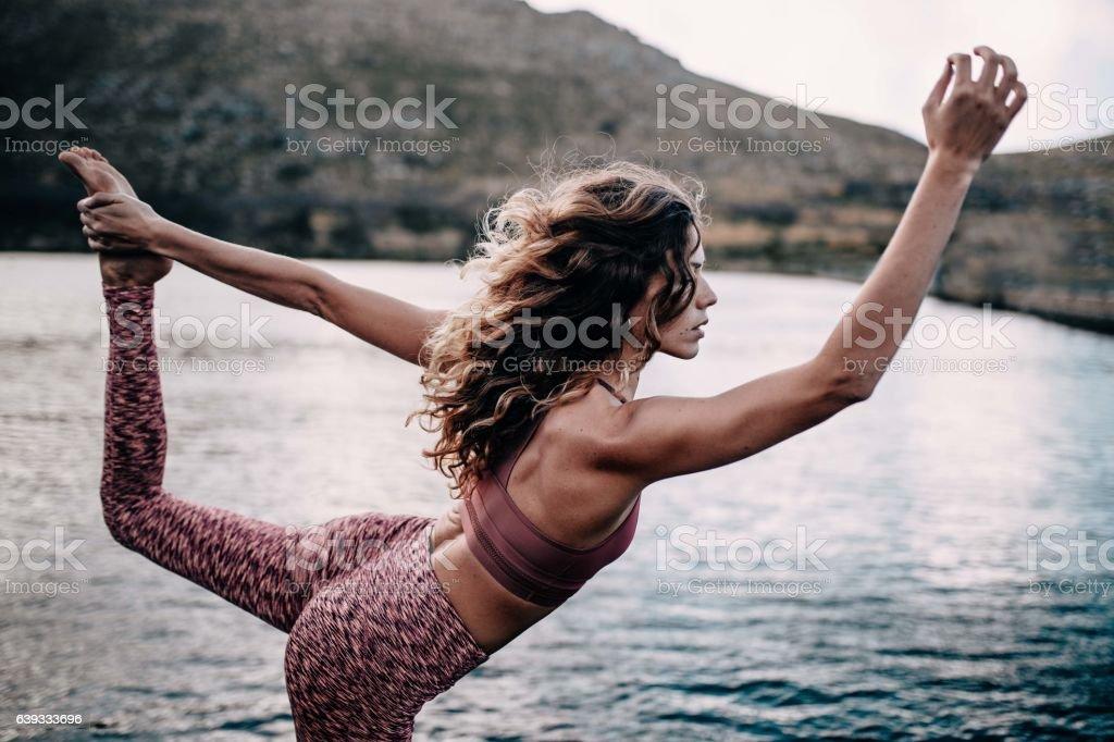 Beautiful young female adult doing yoga pose at lake stock photo