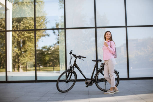 Beautiful young female cyclist drinks warm coffee from a cup by the electric bicycle in the urban environment stock photo