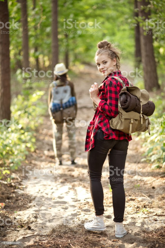 Beautiful young female explorer hiking in forest Portrait of beautiful female explorer hiking with backpack. Young woman is with friend in forest. They are exploring together during summer vacation. 20-24 Years Stock Photo