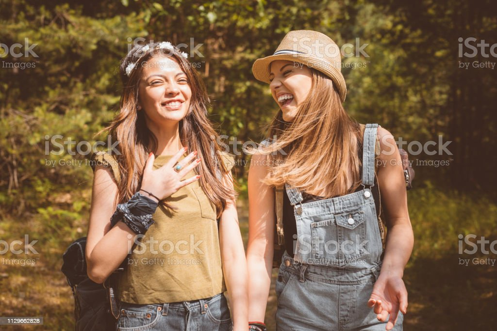 Beautiful young female friends laughing in forest Beautiful young friends laughing in forest. Multi-ethnic females are hiking during weekend. Hipsters are enjoying together. 20-24 Years Stock Photo