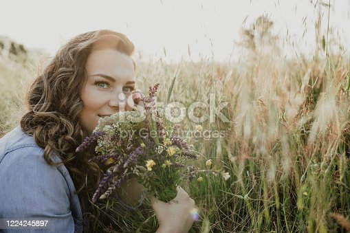 Young beautiful woman having fun in the spring nature, positive emotion and holding handful of spring flowers