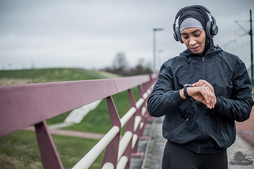 Beautiful Young Female Jogger wearing a sports hijab exercising outdoors in the Netherlands during a training session