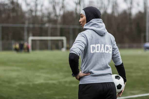 Beautiful Young Female Muslim Soccer Coach Beautiful Young Female Athlete wearing a sports hijab on at an outdoor football sporting complex as a soccer coach religious veil stock pictures, royalty-free photos & images