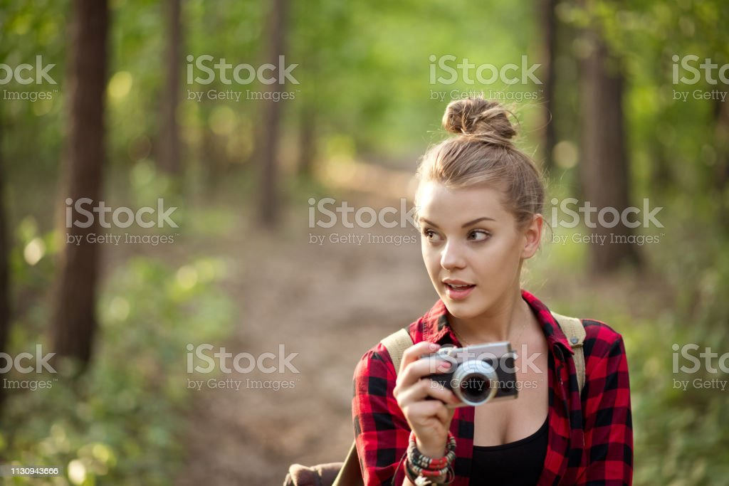 Beautiful young female photographing in forest Blond young woman photographing with digital camera. Beautiful hipster is hiking in forest. Female explorer is with hair bun. 20-24 Years Stock Photo