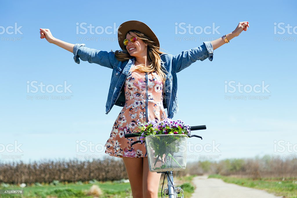 Hermosa mujer joven con una bicicleta vintage en el campo. - foto de stock