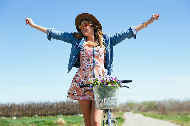 A beautiful young female riding a vintage bicycle in a field stock photo