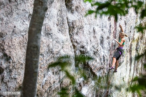 Focused and motivated young female rock climber in the jungle in Brazil near Rio De Janeiro