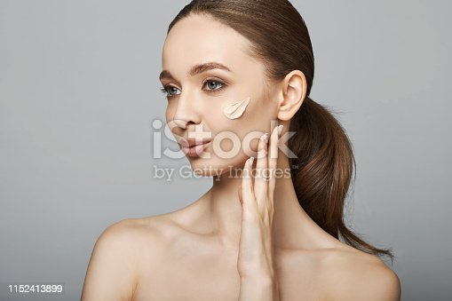 istock Beautiful Young Female With Smooth Skin and foundation Stripes On Face. 1152413899