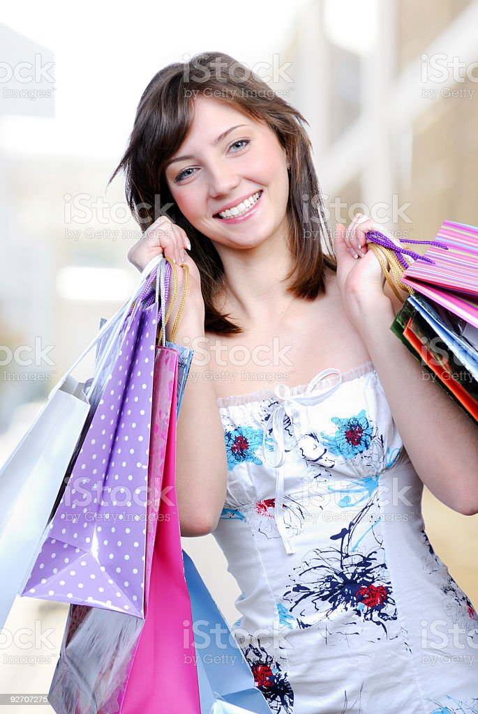 Beautiful young femlae holding colored bags with purchase royalty-free stock photo