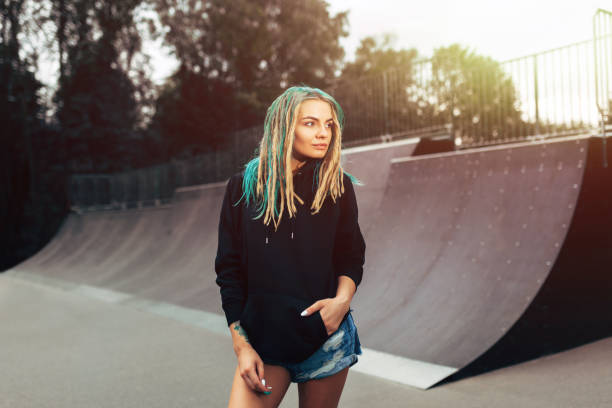 Beautiful young fitness woman in black hoodie standing skate park. stock photo