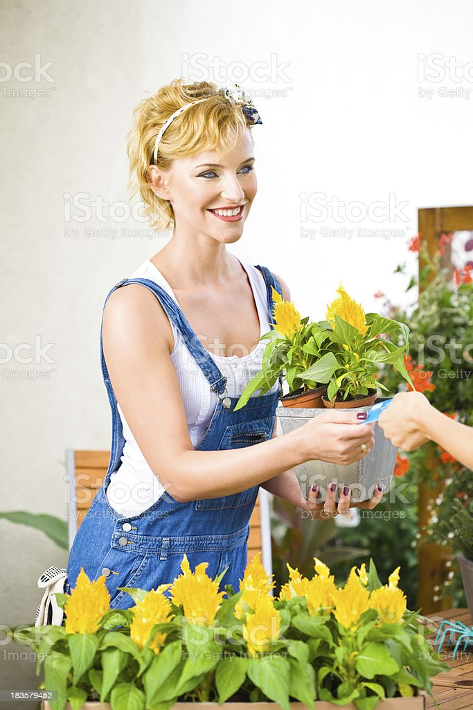Beautiful young florist selling flowers royalty-free stock photo