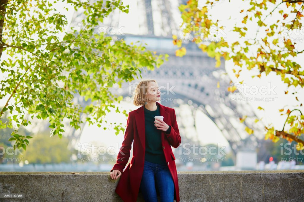 Beautiful young French woman near the Eiffel tower in Paris stock photo