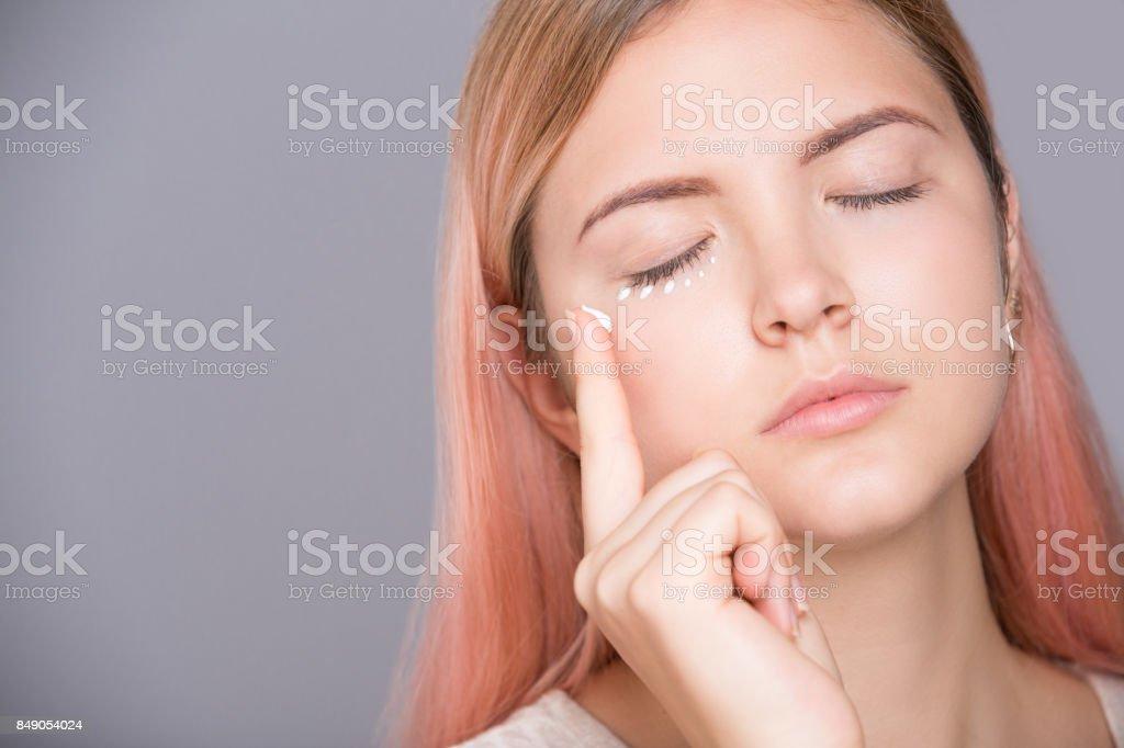 Schöne junge Mädchen auftragen kosmetische Creme auf die Haut um die Augen – Foto