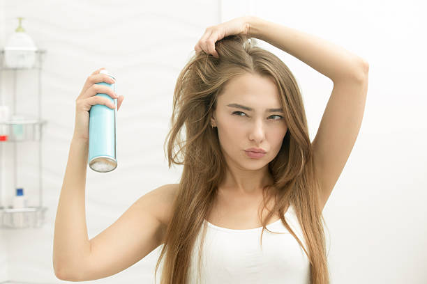 beautiful young girl applying hair spray on her hair - 髪型 ストックフォトと画像
