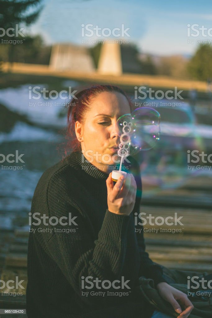 Beautiful young girl blowing soap bubbles outdoors. royalty-free stock photo
