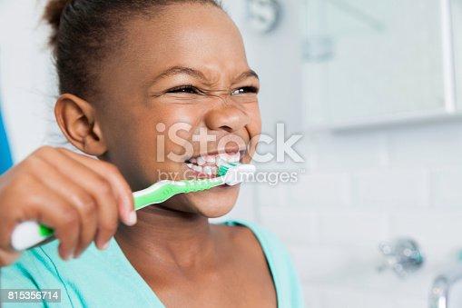 istock Beautiful young girl brushing her teeth. 815356714