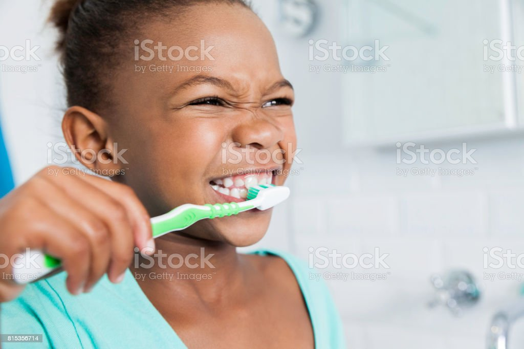 Beautiful young girl brushing her teeth. stock photo