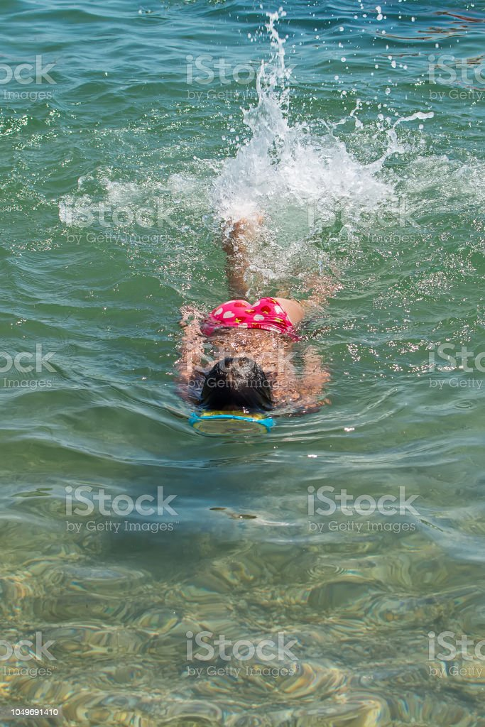 Beautiful Young Girl Diving at sea stock photo