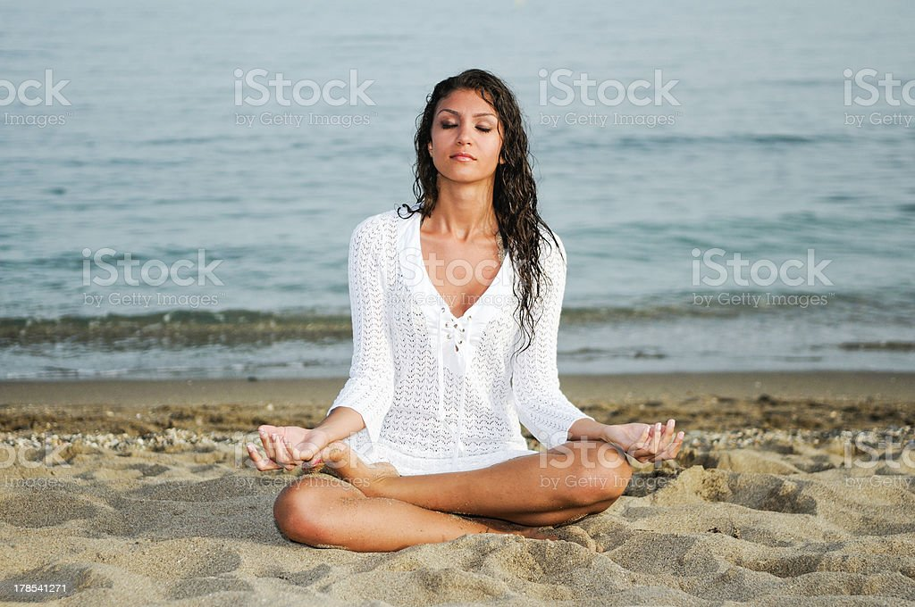 Beautiful young girl doing yoga on the beach royalty-free stock photo