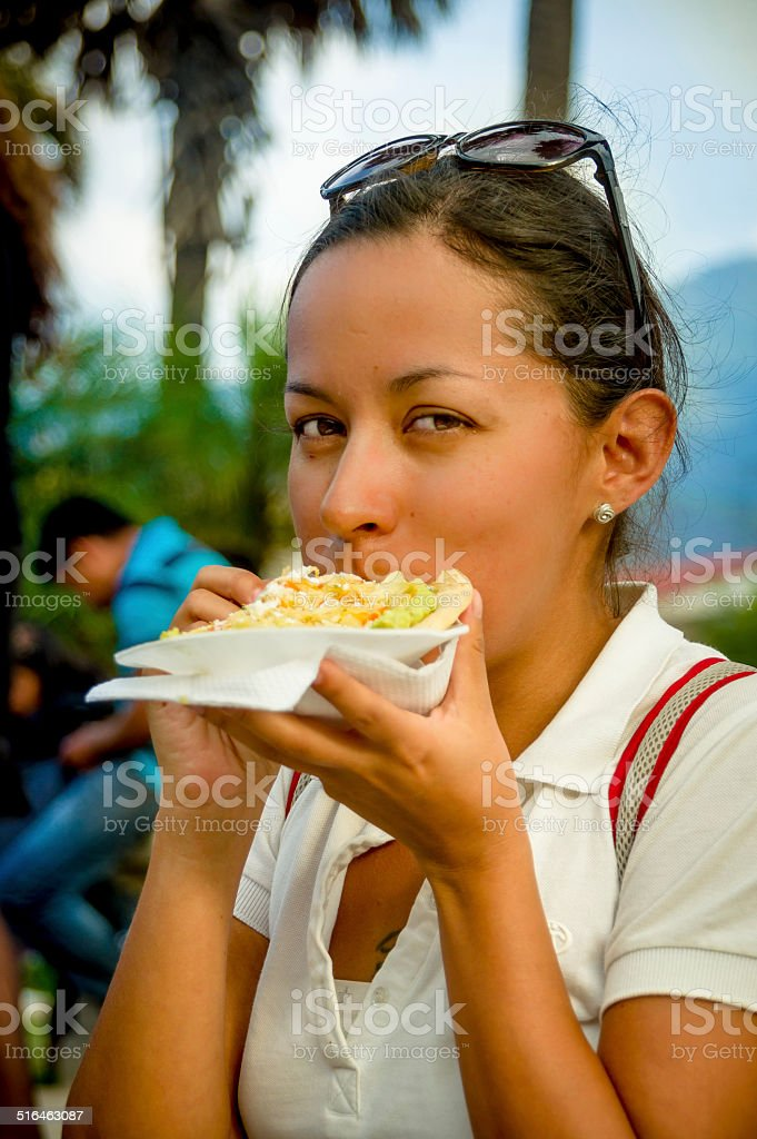 beautiful young girl eating a tostada soft taco stock photo