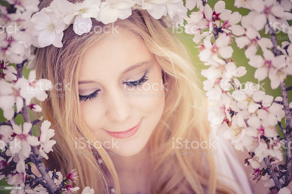 beautiful young girl framed with almond blossom stock photo