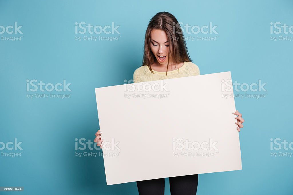 Beautiful young girl holding empty blank board over blue background stock photo