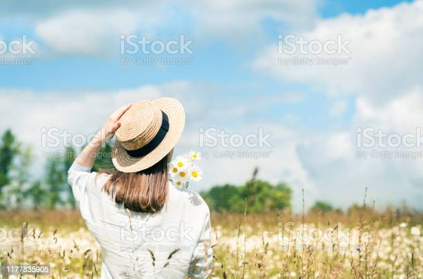 Photo of Beautiful young girl in a hat with a bouquet of field daisies looks at the blue sky on a sunny summer day.