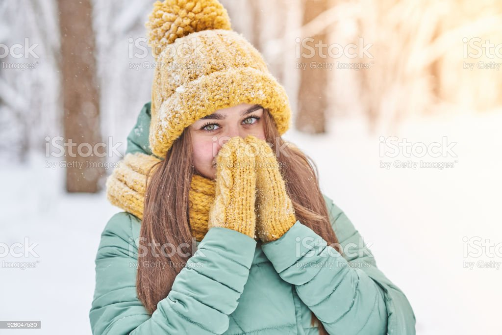 A beautiful young girl in a knitted hat warms her hands in winter stock photo