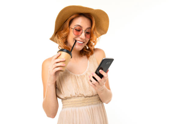 beautiful young girl in a summer image with a phone and a glass of cocktail on a white background stock photo