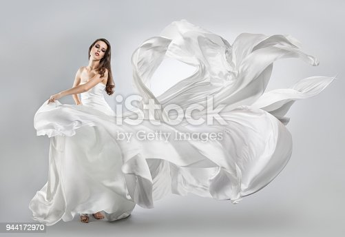 istock beautiful young girl in a white dress. Flying fabric. 944172970