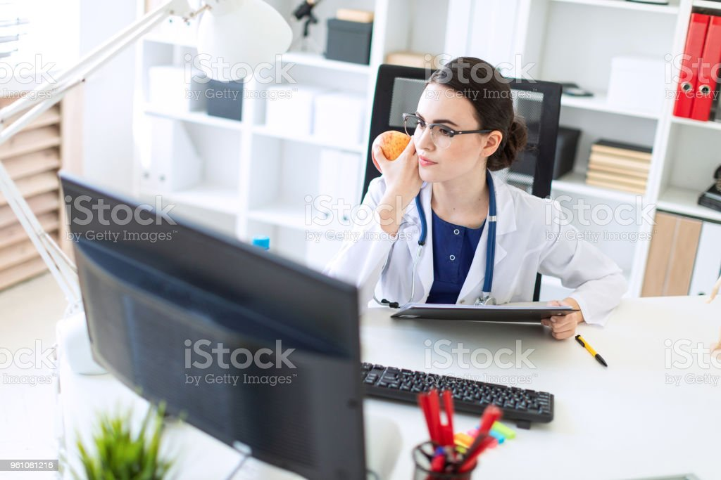 A beautiful young girl in a white robe is sitting at a computer desk with documents and an apple in her hands. stock photo