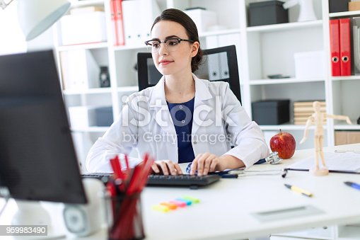 istock A beautiful young girl in a white robe is sitting at the table and typing on the keyboard. 959983490