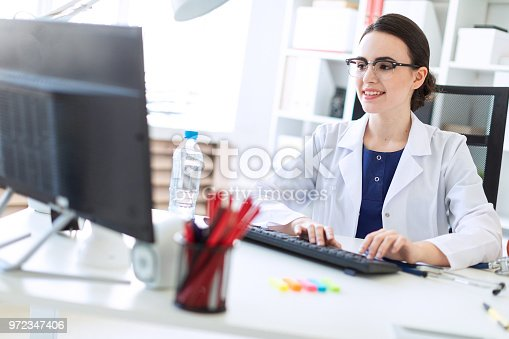 istock A beautiful young girl in a white robe is sitting at the table and typing on the keyboard. 972347406