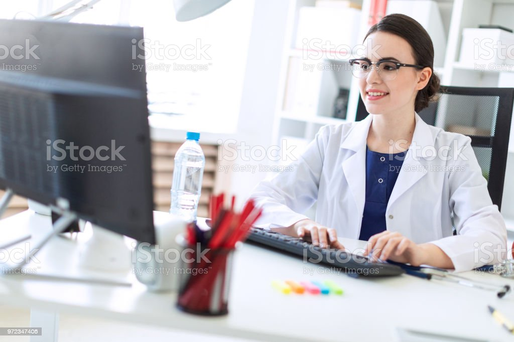 A beautiful young girl in a white robe is sitting at the table and typing on the keyboard. stock photo