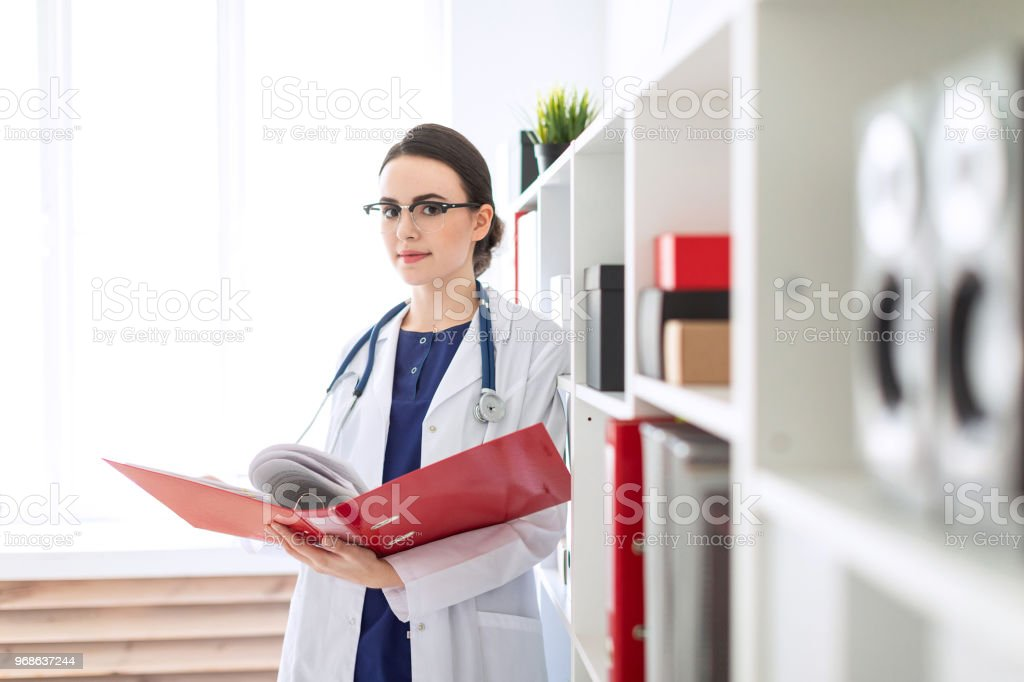 A beautiful young girl in a white robe is standing near the shelter and flips through a red folder with documents. stock photo