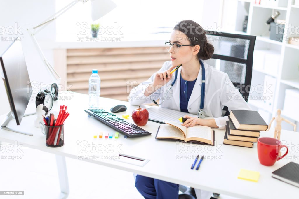 A beautiful young girl in a white robe sits at a table, holds a marker and a pen in her hand and works with a computer and documents. stock photo