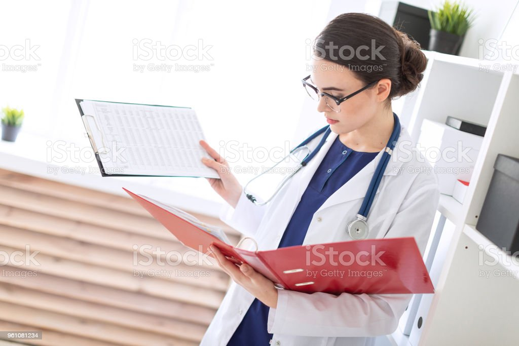 A beautiful young girl in a white robe stands near the shelter and holds in her hands sheets with records and a folder with documents. stock photo