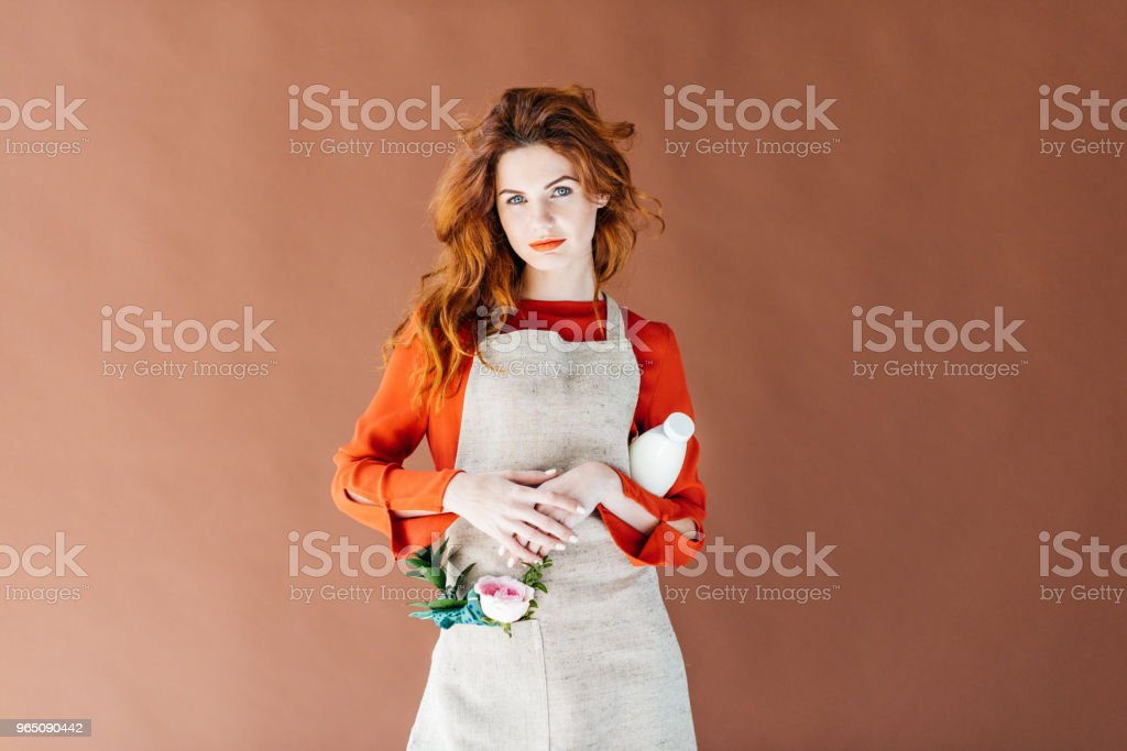 Beautiful young girl in apron holding milk bottle isolated on brown background royalty-free stock photo