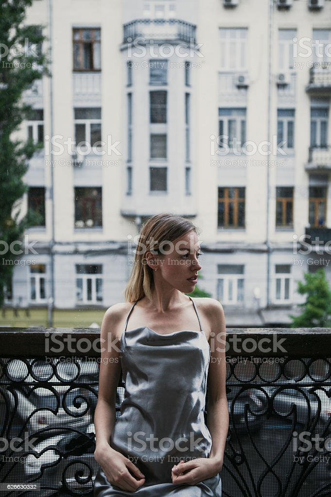 Beautiful young girl in backless satin dress enjoyng the rain stock photo