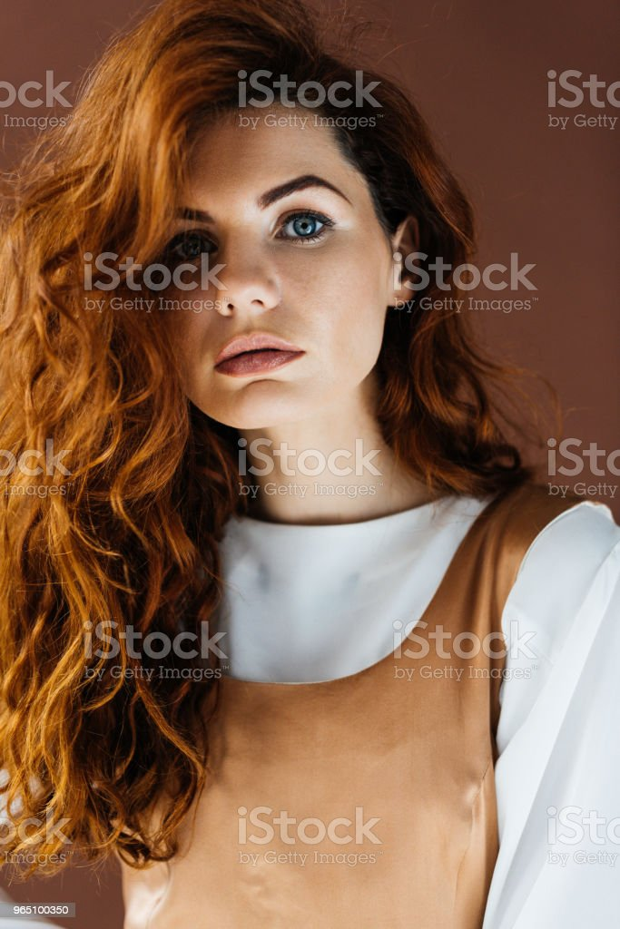 Beautiful young girl in beige dress isolated on brown background zbiór zdjęć royalty-free