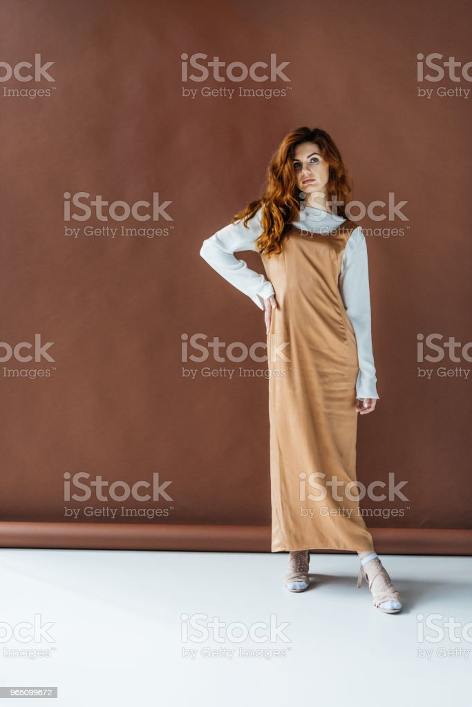 Beautiful young girl in beige dress posing on brown background royalty-free stock photo