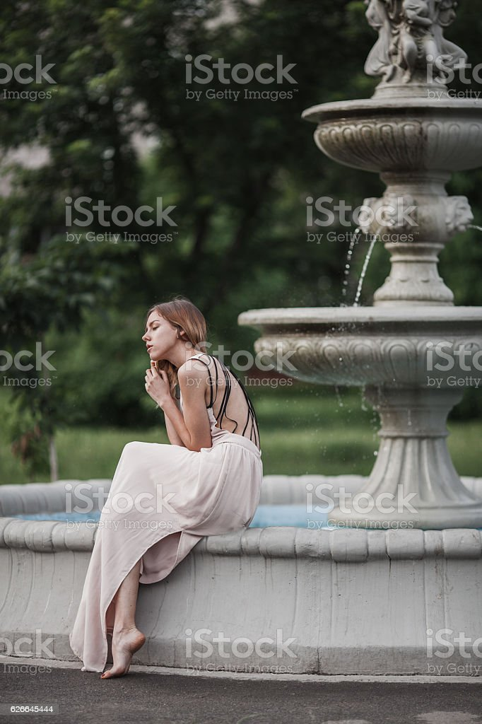 Beautiful young girl in fashionable pink dress sitting near vintage stock photo
