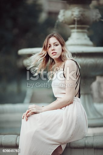 Beautiful young girl in fashionable pink dress standing near vintage stone fountain.