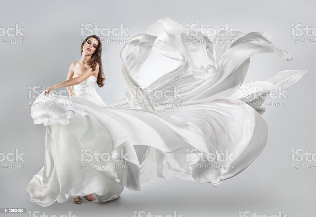 0a883cf0bec219 mooi jong meisje in een witte jurk vliegen. Vloeiende stof royalty free  stockfoto