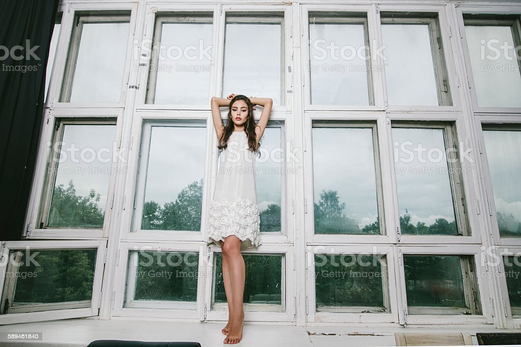 Beautiful young girl in jeans and top posing stock photo