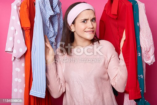 istock Beautiful young girl in pink shirt has shopping in fashion boutique. Pretty lady chooses dress in clothes store. Woman finds modern dress while curving her lips. Upset female dislikes blouses. 1134556608